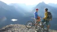 Mountain bikers have conversation at mountain summit