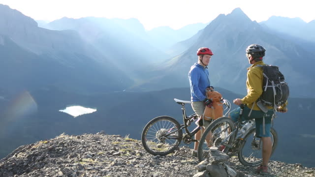 Mountain bikers have conversation at mountain summit