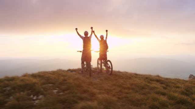 PAN mountain bikers reaching the top at sunset