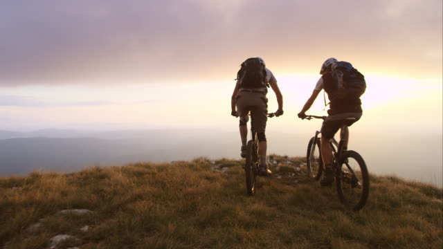 TS Mountain bikers reaching top at sunset and raising hands