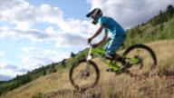 Mountain bikers ride along mountain ridge crest, descend