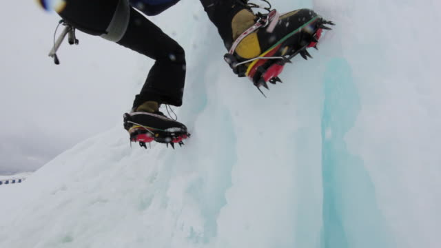 MS TU Mountain climber digging clamp on ice and climbing on ice covered mountain in Austrian Alps / Stubai Glacier, Tirol, Austria