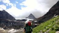 Mountain climber walks along mountain trail towards towering peak