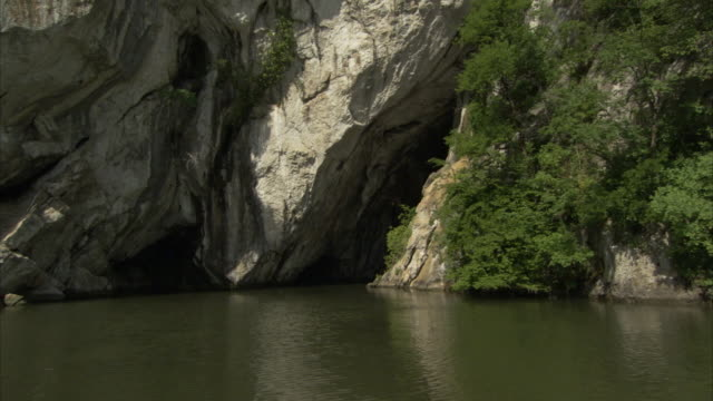 A mountain jutting up from a lake is pocked with caves.
