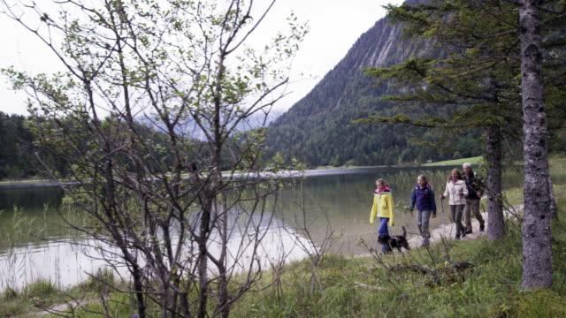 mountain lake, family walking with dog, distance shot