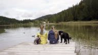 mountain lake, girls sitting on lake, dog, from behind, pan shot