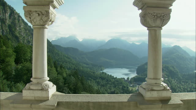 WS Mountain landscape and Lake Starnberg seen from Neuschwanstein Castle, columns in foreground, Bavaria, Germany