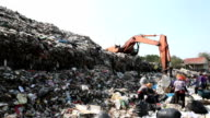 mountain of garbage with people and working backhoe