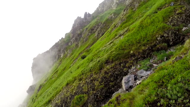 Mountain side in the cloud. Hikers