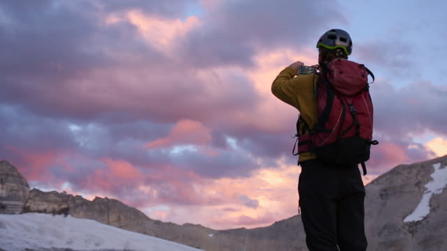 Mountaineer arrives at glacial edge at sunrise