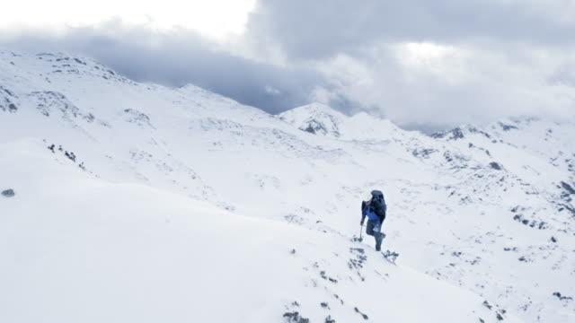 Luchtfoto bergbeklimmer veroveren de berg met stijgijzers en sneeuw bijl