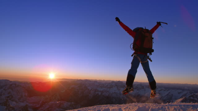 SLO MO Mountaineer jumping joyously on a snowy mountain top at sunset