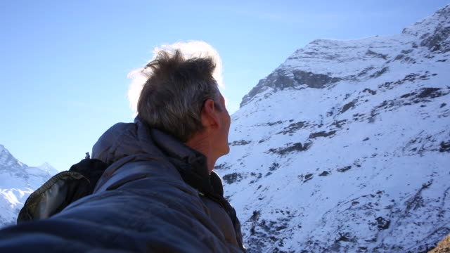 Mountaineer takes selfie on summit, looks out to sunrise