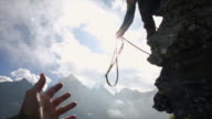 Mountaineer tosses rope to companion, from cliff