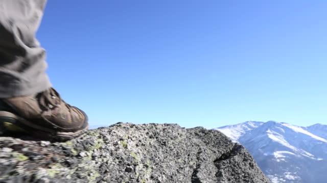 Mountaineer traverses high rock ridge above mountains