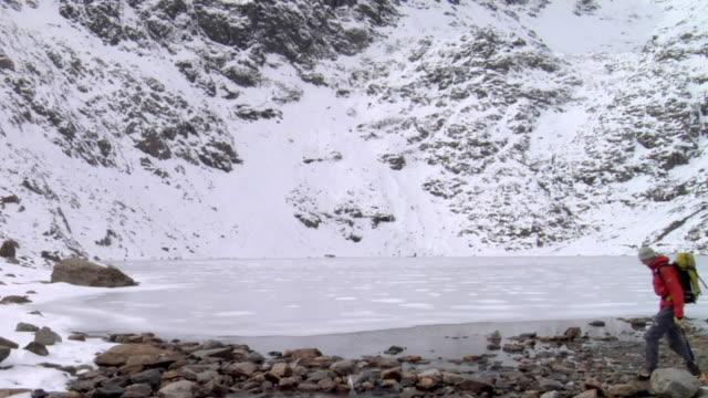WS Mountaineer walking by frozen mountain lake, snow covered mountain in background / Llanberis, Snowdonia, UK