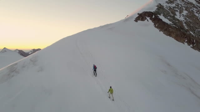 Mountaineers approaching a ridge at sunrise