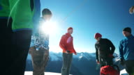 Mountaineers have team meeting at sunrise on mountain summut