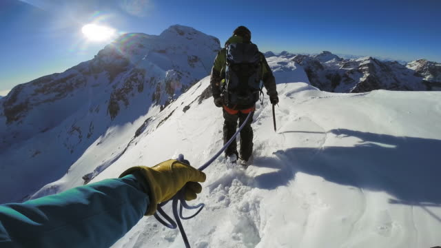 POV Mountaineers on short rope walking across snowy mountain top