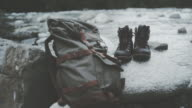 Mountainous landscape. Close up on hiking boots and backpack