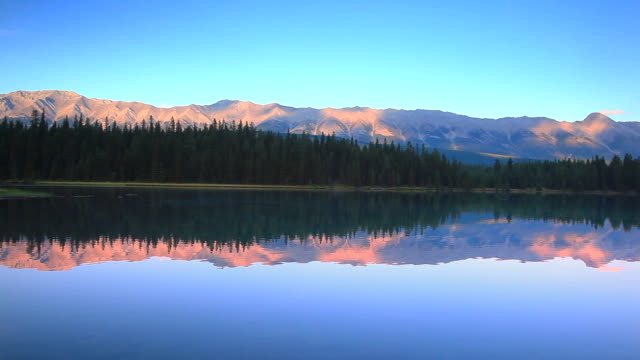 Mountains at sunset reflecting their glow in Alpine Lake