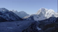Mountains provide shade for a glacial valley in the Himalayas. Available in HD.