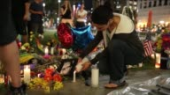 Mourners pay their respects for those lost at a makeshift memorial for the victims of the Pulse nightclub shooting in Orlando Florida on June 14 2016