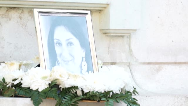 Mourners place flowers in tribute to murdered journalist Daphne Caruana Galizia at the Valletta monument to the Great Siege of 1565