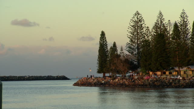 various shots of Port Macquarie Breakwall Holiday Park cabins Norfolk Island pines / looking west to Westport Club / sun setting behind the trees on...