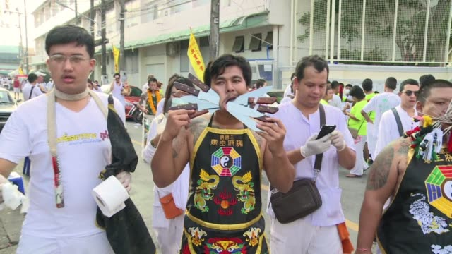Mouths pierced with swords knives and gun barrels at Thailands vegetarian festival make for a bizarre and grotesque spectacular but devotees insist...