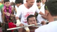 Mouths pierced with swords knives and gun barrels at Thailand's vegetarian festival make for a bizarre and grotesque spectacular but devotees insist...