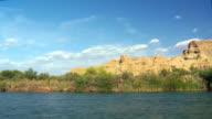 SIDE POV Moving along Colorado River shoreline with bare mountain rocks and green vegetation close to waterline, Blythe, California, USA