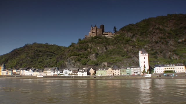 SIDE POV, Moving on river Rhine, water front houses and castle on hill in distance, Sankt Goarshausen, Germany