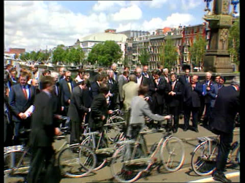 MPs receive bicycle allowance ITN LIB Amsterdam EU leaders including British PM Tony Blair MP onto bicycles and riding along