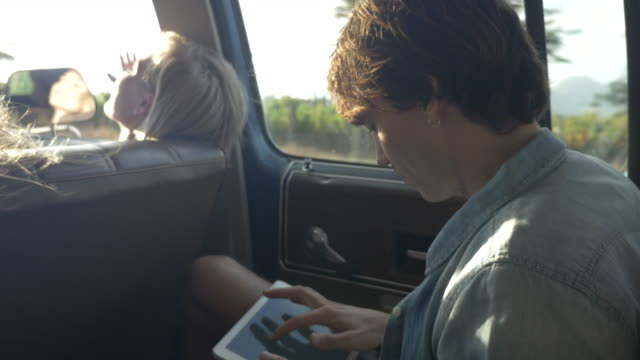 MS_Young man typing on digital tablet, on back seat of old car
