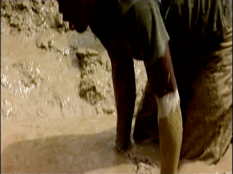 Mud searched for gold and passed along human chain in gold mine eastern Democratic Republic of Congo