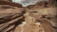 Muddy flood water pours through a sandstone canyon. Available in HD.