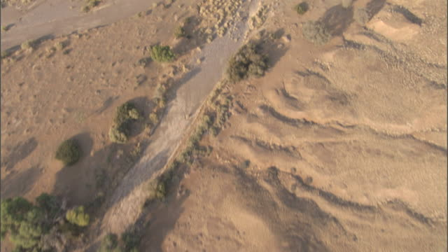 A muddy stream winds through the vast Namib Desert. Available in HD.