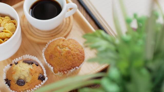 Muffin Kuchen und Gen Lebensmittel mit schwarzen Kaffee Frühstück set auf hölzerne Schüssel und Holztisch, Dolly Schuss rechts nach links