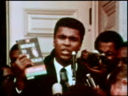 Muhammad Ali by microphone speaking at podium and holding up copy of 'Message To the Black Man' by Elijah Muhammad / crowd listening to him Muhammad...