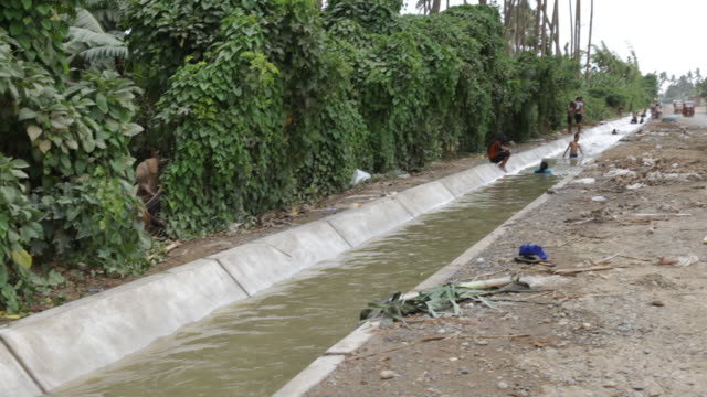 Kids bathing in watering channel where people are washing themselves and getting drinking water next to a banana plantation
