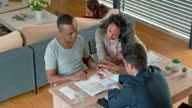 Multi ethnic couple consulting with Caucasian banker at home