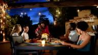 Multi-etnische vrienden eten bij een zomer-BBQ
