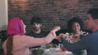 Multi-etnische groep van vrienden samen genieten van maaltijd