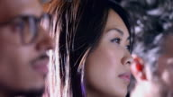 A multi ethnic team of creative employees watch a presentation.