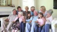 Multi Generation Familie sitzt auf Sofa im Innenbereich