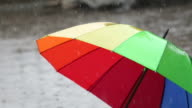 Multi-colored umbrella on sidewalk in rain