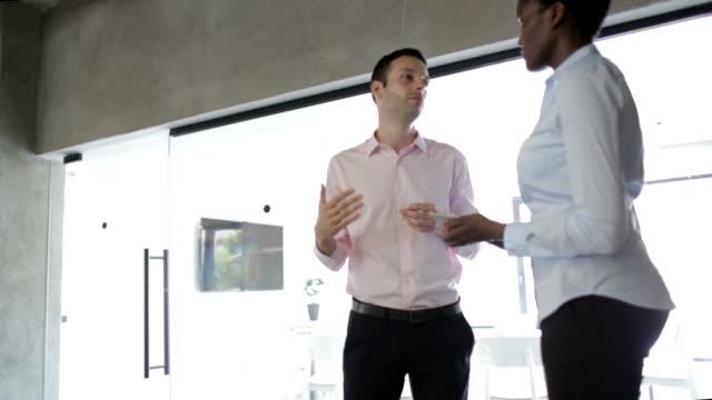 HD: Multi-ethnic Business People Talking Indoors.