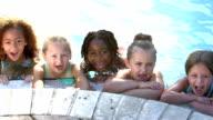 Multi-ethnic children hanging on side of swimming pool