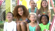Multi-ethnic children in summer, sitting and laughing
